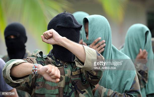 Members of 'Los Rastrojos' bandit group cover their face with towels and balaclavas as they surrender at the Voltigeros Battalion on May 21 2009 in...