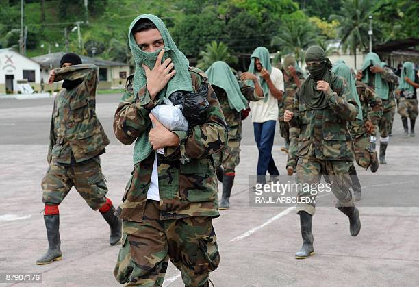 Members of 'Los Rastrojos' bandit group cover their faces as they surrender at the Voltigeros Battalion on May 21 2009 in Uraba Antioquia department...