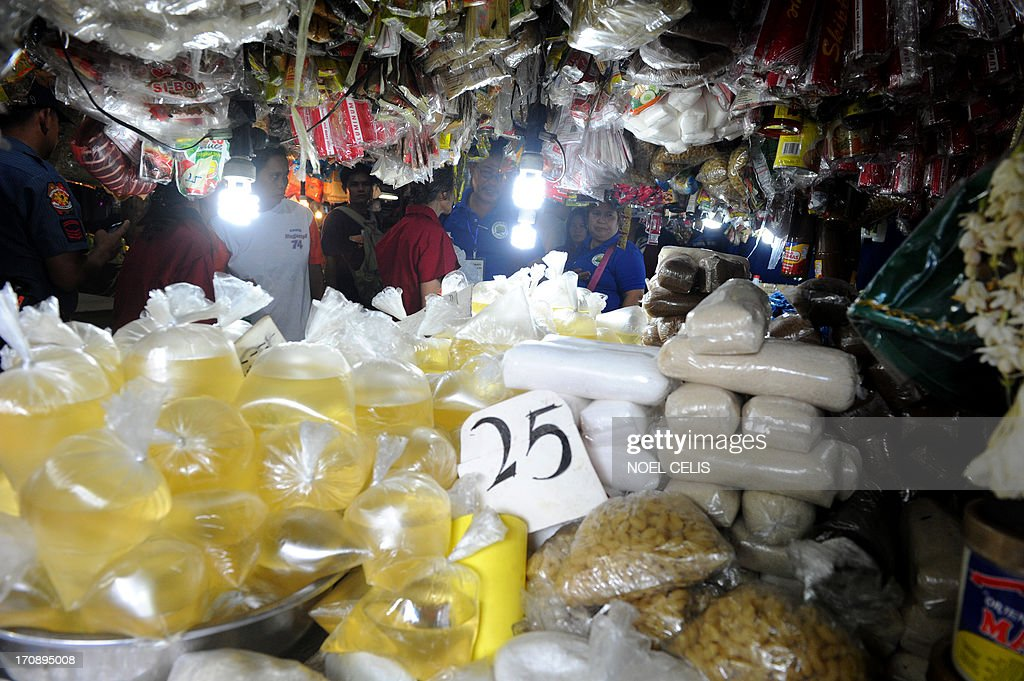 Members of Makati City's Plastic Monitoring Task Force (PMTF), (C) look for prohibited plastic used used by vendors at a wet market in Manila's financial district, Makati City on June 20, 2013. The Philippines' financial centre banned disposable plastic shopping bags and styrofoam food containers on June 20, as part of escalating efforts across the nation's capital to curb rubbish that exacerbates deadly flooding.
