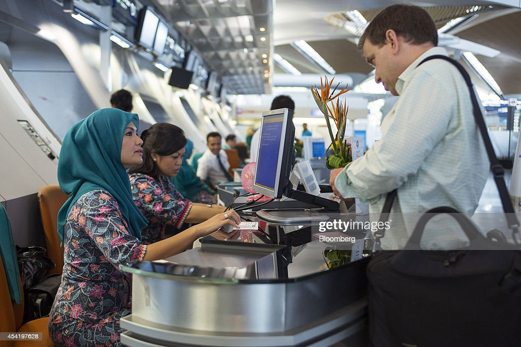 A members of Malaysian Airline System Bhd.'s (MAS) ground staff serves a passenger at the business class check-in counter at Kuala Lumpur International Airport (KLIA) in Sepang, Malaysia, on Tuesday, Aug. 26, 2014. Malaysia Airlines are scheduled to release second quarter earnings Aug. 27 as the airline considers job cuts, a review of aircraft orders and replacing its chief executive officer after the national carrier suffered two disasters this year, people familiar with the plan said. Photographer: Charles Pertwee/Bloomberg via Getty Images