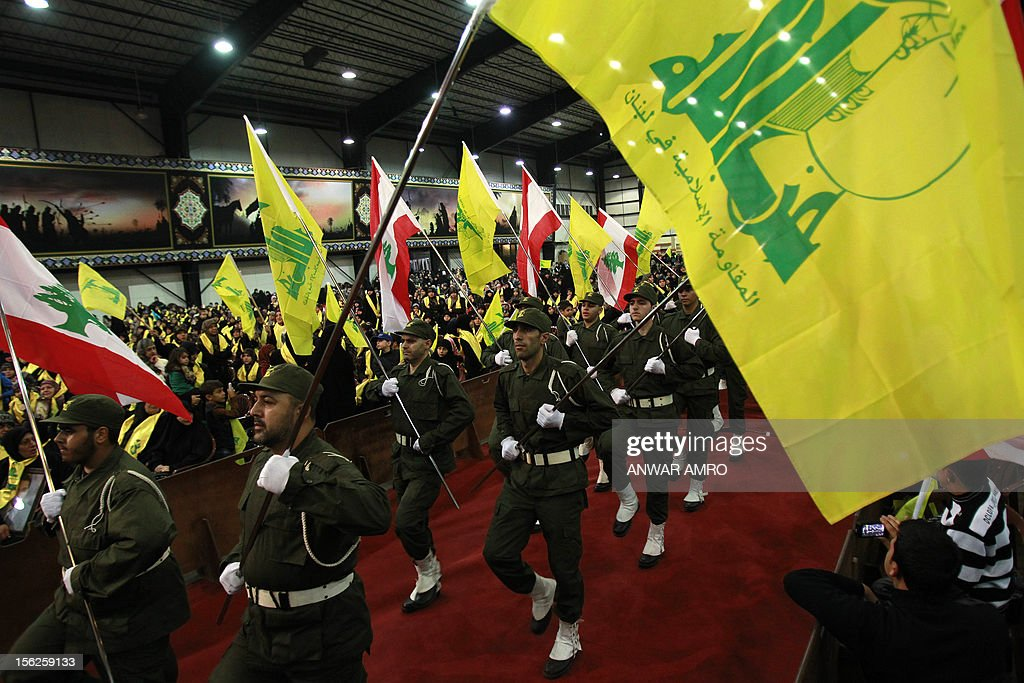 Members of militant Shiite Muslim group Hezbollah wave the Hezbollah flag during a rally organised by Hezbollah marking the party's Martyrs' Day in southern Beirut, on November 12, 2012.