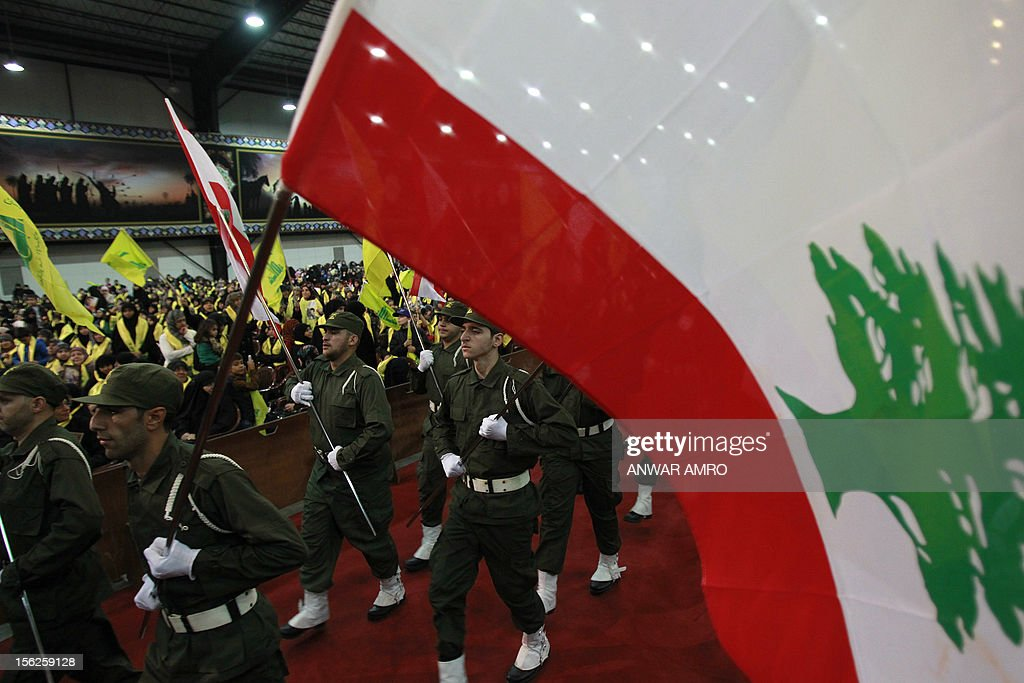 Members of militant Shiite Muslim group Hezbollah wave the Lebanese flag during a rally organised by Hezbollah marking the party's Martyrs' Day in southern Beirut, on November 12, 2012.