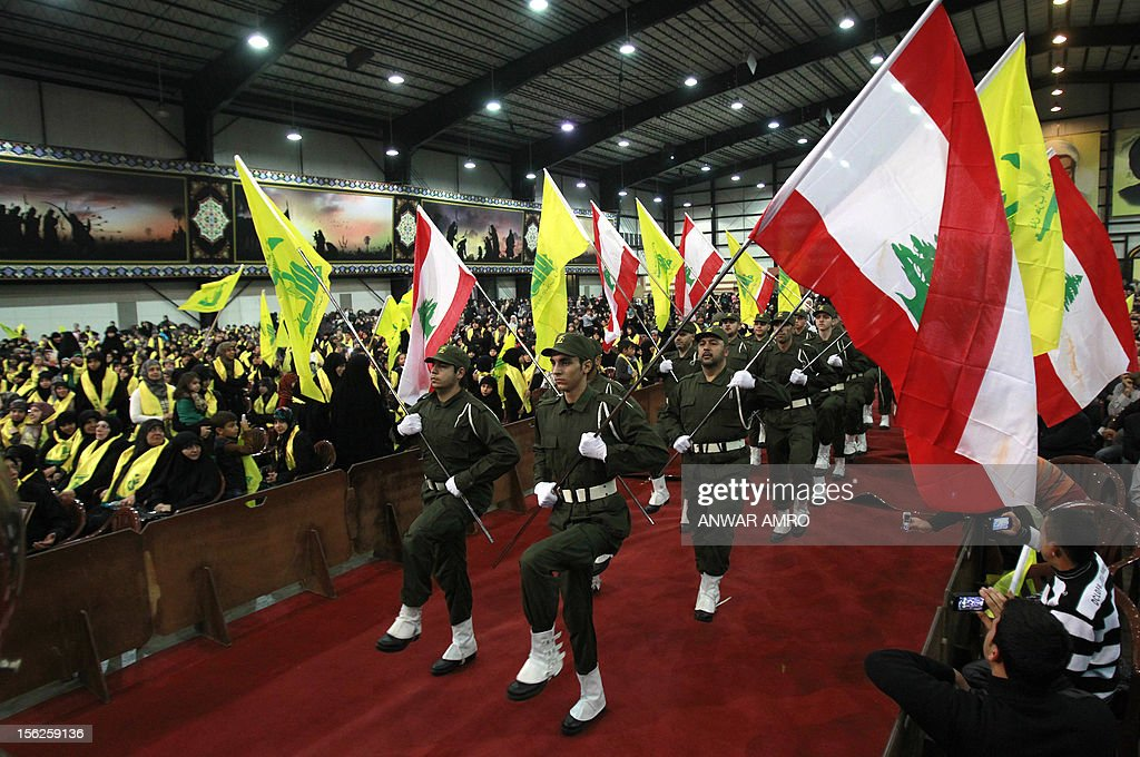 Members of militant Shiite Muslim group Hezbollah wave the Lebanese flag as well as the Hezbollah flag during a rally organised by Hezbollah marking the party's Martyrs' Day in southern Beirut, on November 12, 2012.