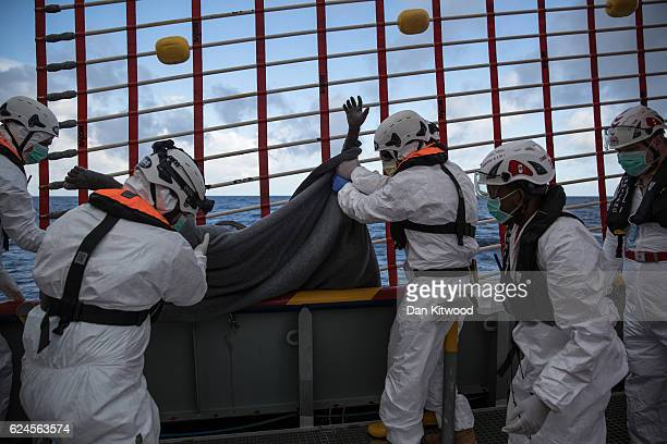 Members of MOAS and the Red Cross hoist the dead body of a man believed to be a refugee who was seen floating with a life jacket approximately 15...