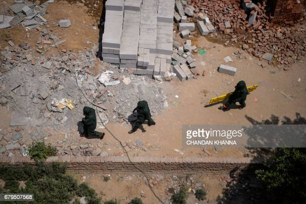 Members of National Disaster Response Force inspect the premises of a government school whose students were admitted to hospital after being affected...
