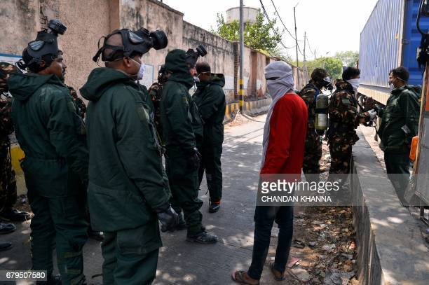 Members of National Disaster Response Force prepare to take part in the cleanup operation at a container depot where a gas leak occurred in New Delhi...