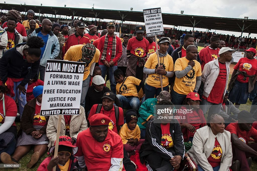 Members of National Union of Metalworkers of South Africa (NUMSA), one of the biggest South African unions that was expelled from the main South African Trade Unions Federation (COSATU), hold signs during a May Day rally organized by a new United Front South African labour movement at Tembisa stadium on May 1, 2016 in Tembisa. Vavi was expelled from Cosatu in March 2015 for bringing it into disrepute and causing divisions by speaking out against the ANC governments policies and saying it had failed workers. He had since launched a new union federation to rival Cosatu. / AFP / JOHN