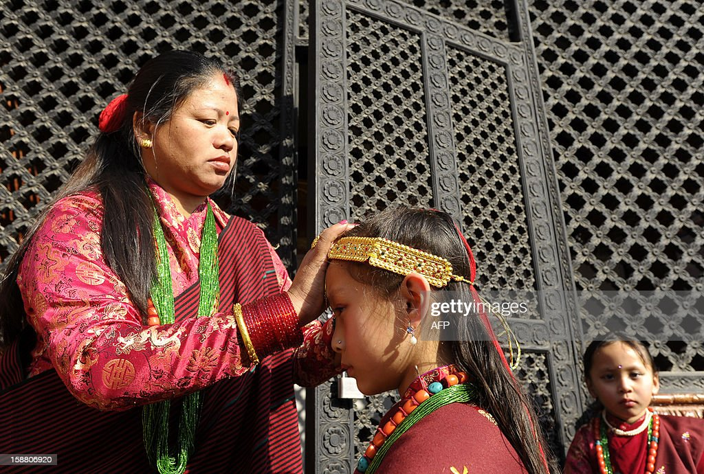 Members of Nepal's indigenous Gurung community adjust their traditional dress as they prepare to take part in a ceremony in Kathmandu on December 30, 2012, held to celebrate their New Year or Lhosar. Gurungs number some 700,000 people about three percent of the Himalayan nation's population and are mainly concentrated in the country's central region. AFP PHOTO/Prakash MATHEMA