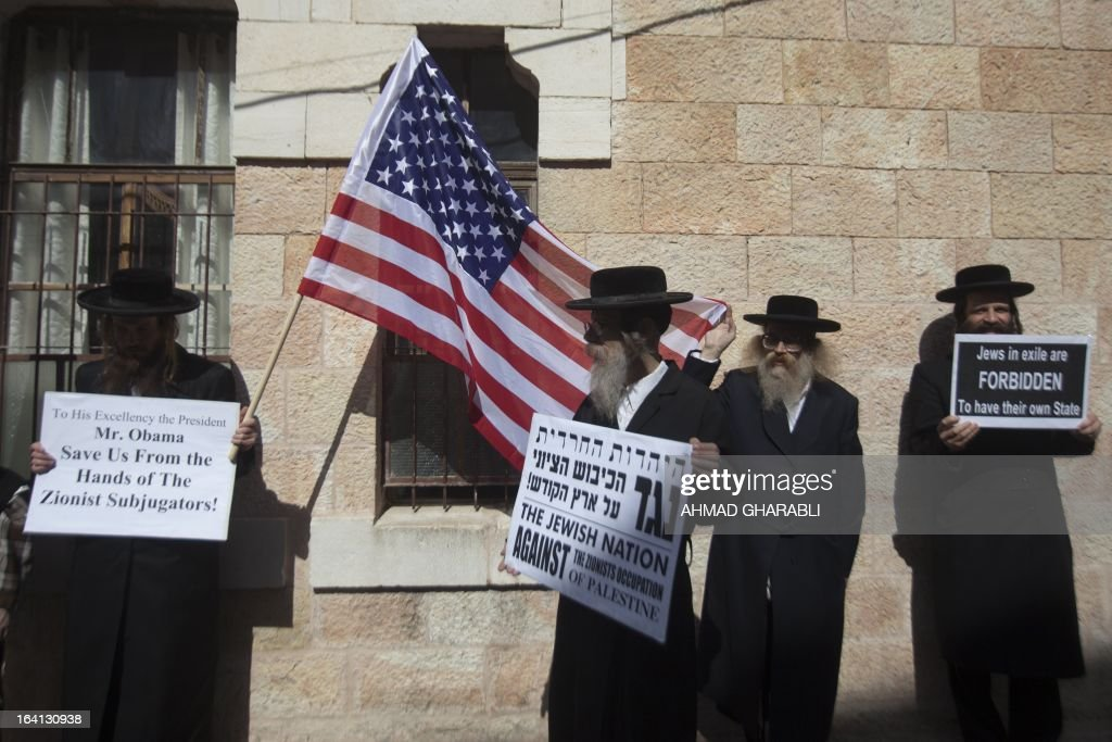 Members of Neturei Karta, a small faction of anti-Zionist ultra-Orthodox Jews who oppose Israel's existence, hold up placards and a US flag during a rally in Jerusalems Mea Sharim district held on March 20, 2013 as US President Barrack Obama landed in Israel for the first time as US president, on a mission to ease past tensions with his hosts and hoping to paper over differences on handling Iran's nuclear threat.