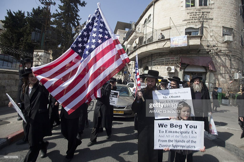 Members of Neturei Karta, a small faction of anti-Zionist ultra-Orthodox Jews who oppose Israel's existence, hold up placards and US flags during a rally held in Jerusalem's Mea Sharim district on March 20, 2013 as US President Barrack Obama landed in Israel for the first time as US president, on a mission to ease past tensions with his hosts and hoping to paper over differences on handling Iran's nuclear threat.