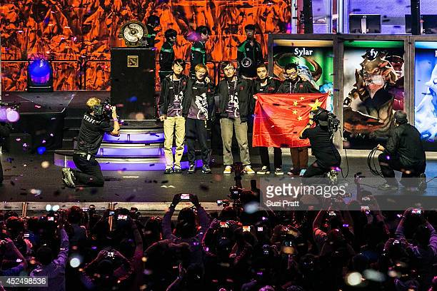Members of Newbee pose on stage following their win at The International DOTA 2 Championships on July 21 2014 in Seattle Washington