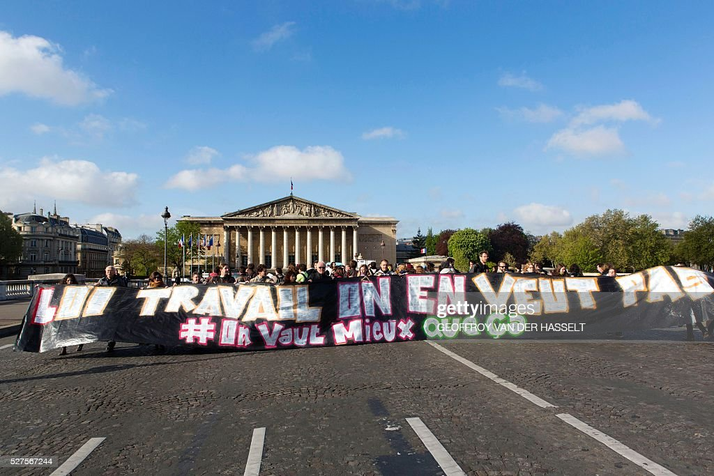 Members of Nuit Debout movement hold a banner reading 'Labour reforms we don't want it' in front of the French parliament as they protest against the controversial labour reforms in Paris, on May 3, 2016. About sixty Nuit Debout movement protesters stopped the traffic on Tuesday for several minutes on the Concorde bridge to raise members of parliament's awareness on their opposition to the controversial El-Khomri labour reforms a few hours before its vote at the Palais Bourbon. / AFP / Geoffroy Van der Hasselt