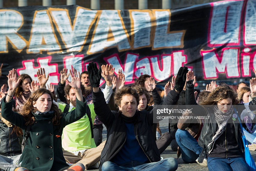 Members of Nuit Debout movement raise their hands during a sitting protest as they demonstrate against the controversial labour reforms in Paris, on May 3, 2016. About sixty Nuit Debout movement protesters stopped the traffic on Tuesday for several minutes on the Concorde bridge to raise members of parliament's awareness on their opposition to the controversial El-Khomri labour reforms a few hours before its vote at the Palais Bourbon. / AFP / Geoffroy Van der Hasselt