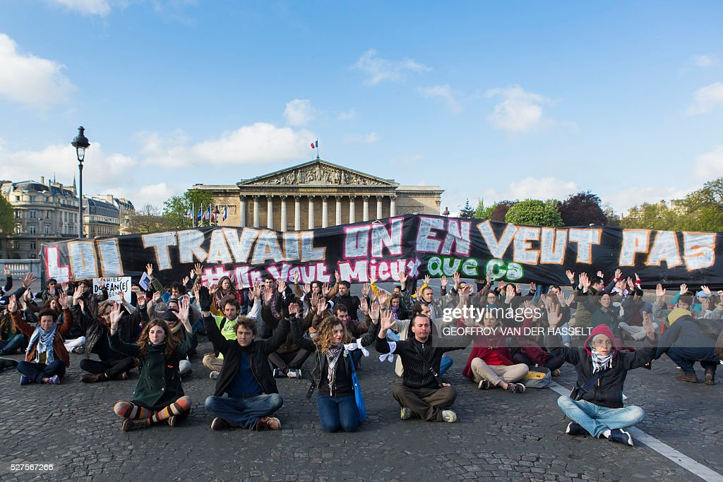 Members of Nuit Debout movement sit and hold a banner reading 'Labour reforms we don't want it' in front of the French parliament as they protest against the controversial labour reforms in Paris, on May 3, 2016. About sixty Nuit Debout movement protesters stopped the traffic on Tuesday for several minutes on the Concorde bridge to raise members of parliament's awareness on their opposition to the controversial El-Khomri labour reforms a few hours before its vote at the Palais Bourbon. / AFP / Geoffroy Van der Hasselt