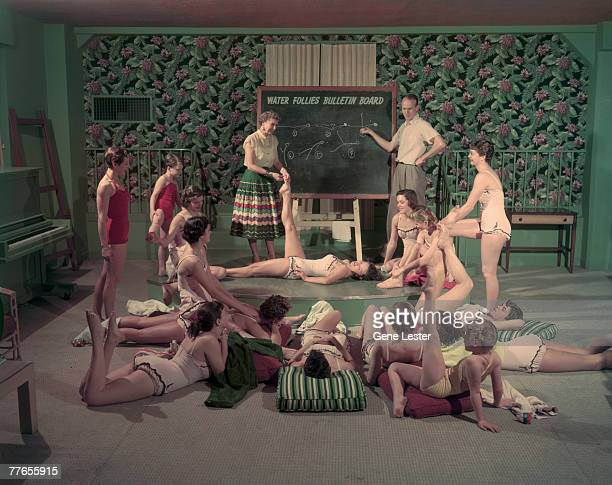 Members of Oakland California's Athens Club synchronized swimming team discuss strategy and leg positions using a chalkboard February 1955 The...