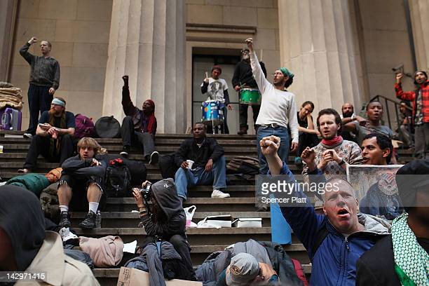Members of Occupy Wall Street gather on the steps of Federal Hall after being evicted from the sidewalk early in the morning where they had been...