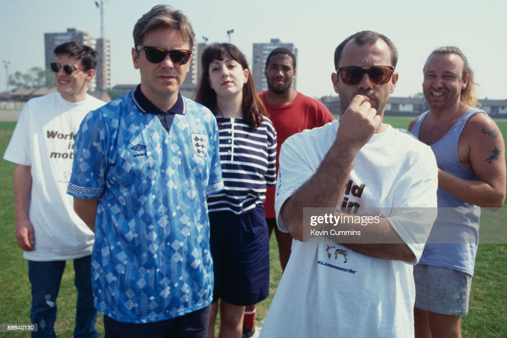 Members of of English rock group New Order with comedian Keith Allen and footballer John Barnes after they recorded the official song of the England football team's 1990 World Cup campaign, 'World in Motion', 5th May 1990. Left to right: drummer Stephen Morris, singer Bernard Sumner, keyboard player Gillian Gilbert, footballer John Barnes, comedian Keith Allen and bassist Peter Hook. Allen wrote the words to the song, while Barnes contributed a rap to the recording, which was released under the name EnglandNewOrder.