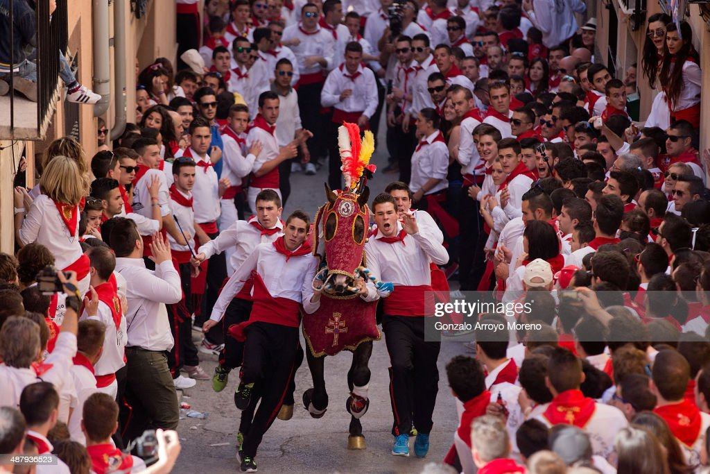 Members of one of Caravaca«s Wine Horse clubs make a room with their horse over the crowd at Simona's slope prior to the Running of the Wine Horses at Cravaca Castle slope on May 2, 2014 in Caravaca De La Cruz, Spain. The Day of the Wine Horses is part of May Caravaca Cross Festivities. Each year 60 horses try to do the best time across 80 meters ridden by four men running alongside them. The tradition goes back to the 13th Century and it is inspired in a legend of Templar knights evading the Muslim siege around the city. The horses are harnessed with ornamental capes and are exhibited around the city prior to the race.