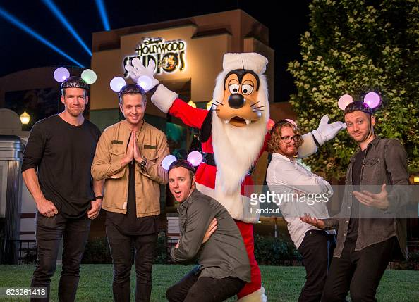 Members of OneRepublic pose with Goofy Nov 13 2016 after taping for the ABC holiday TV specials 'The Wonderful World of Disney Magical Holiday...