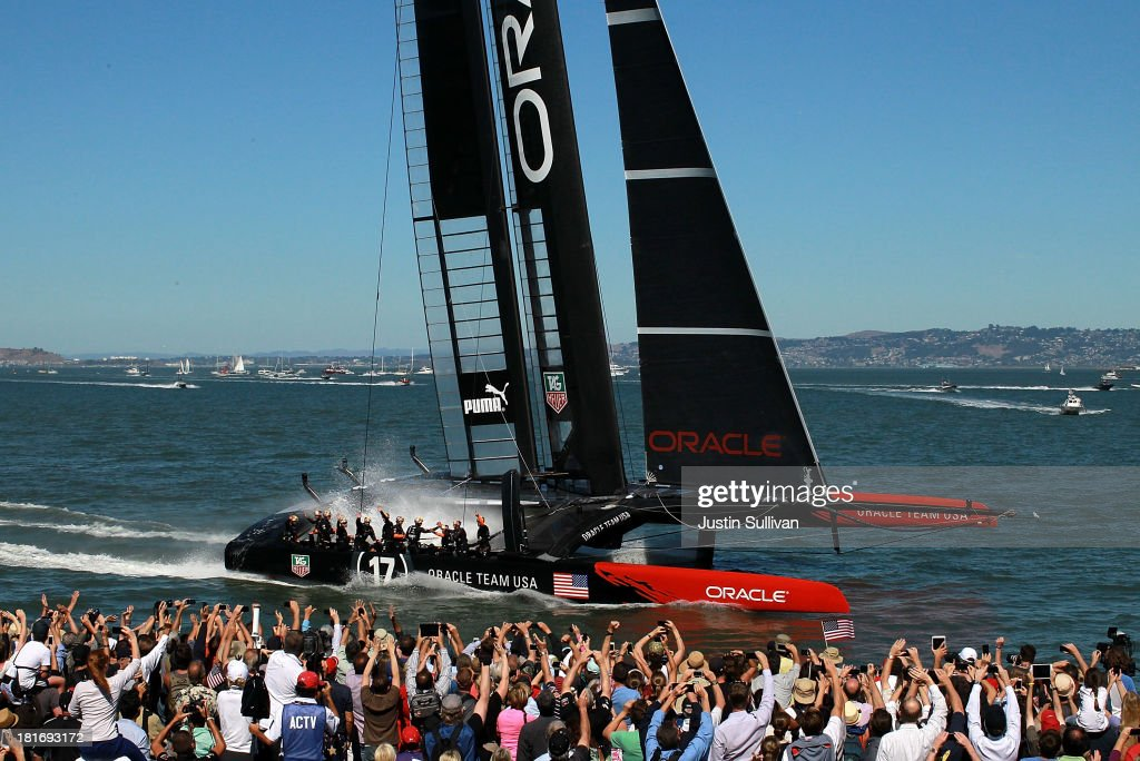 Members of Oracle Team USA skippered by James Spithill cross the finish line to defeat Emirates Team New Zealand skippered by Dean Barker during race...