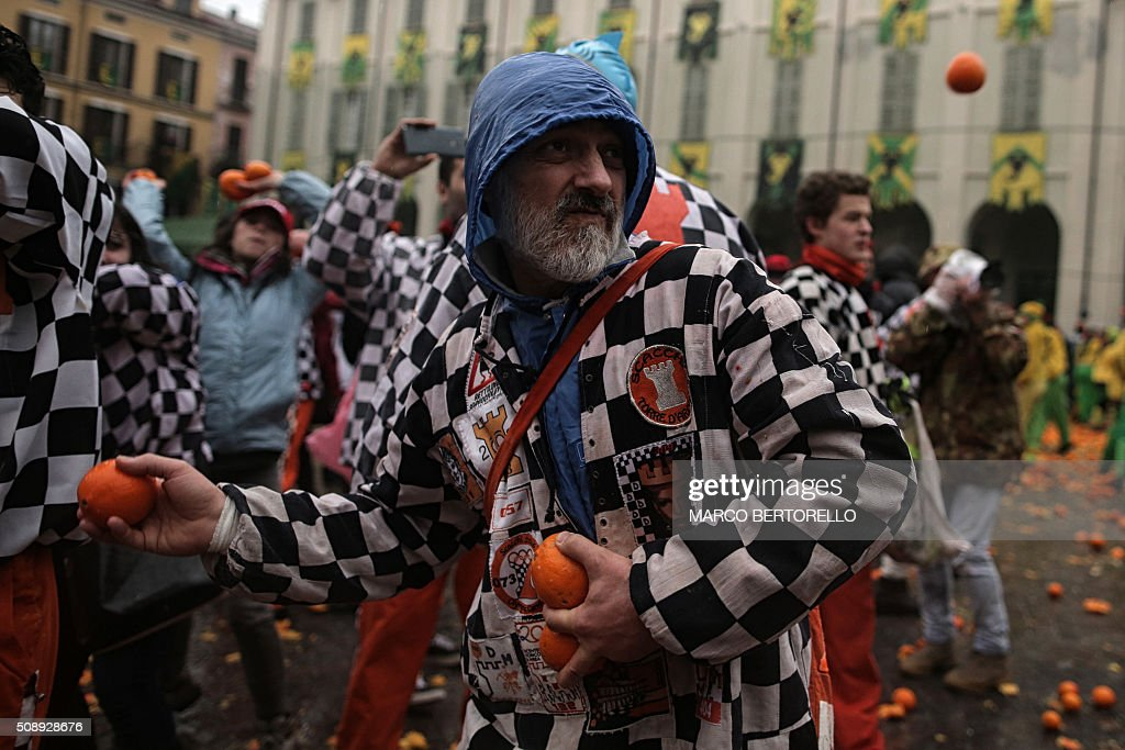 Members of orange battle teams take part in the traditional 'battle of the oranges' held during the carnival in Ivrea, near Turin, on February 7, 2016. During the event which marks the people's rebellion against tyrannical lords who ruled the town in the Middle Ages, revellers parading on floats represent guards of the tyrant, while those on foot the townsfolk. / AFP / MARCO BERTORELLO
