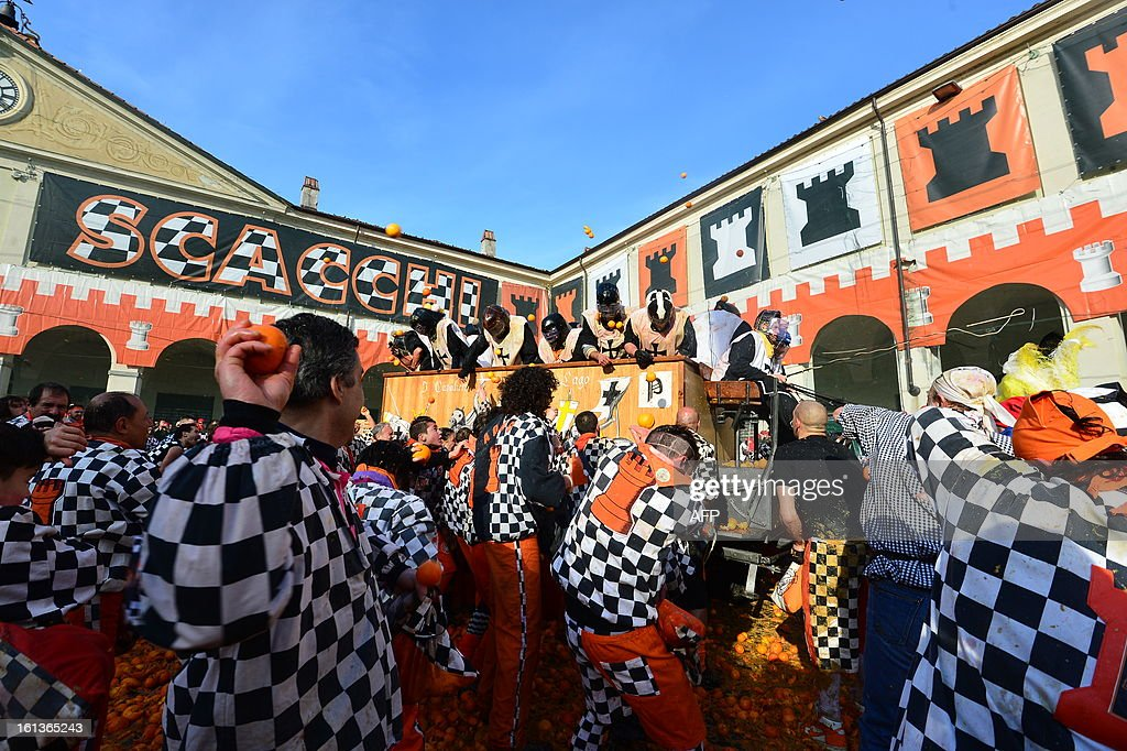 Members of orange battle teams throw oranges at each other during the traditional 'battle of the oranges' held during the carnival in Ivrea, near Turin, on February 10, 2013. During the event which marks the people's rebellion against tyrannical lords who ruled the town in the Middle Ages, revellers parading on floats represent guards of the tyrant, while those on foot the townsfolk. AFP PHOTO / GIUSEPPE CACACE