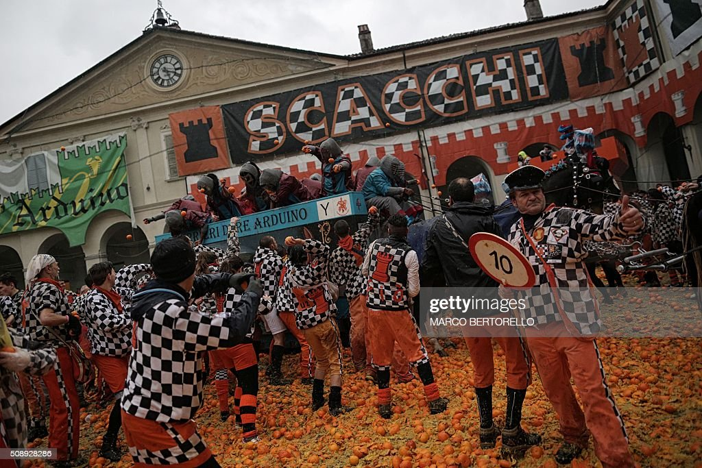 Members of orange battle teams throw oranges at each other during the traditional 'battle of the oranges' held during the carnival in Ivrea, near Turin, on February 7, 2016. During the event which marks the people's rebellion against tyrannical lords who ruled the town in the Middle Ages, revellers parading on floats represent guards of the tyrant, while those on foot the townsfolk. / AFP / MARCO BERTORELLO