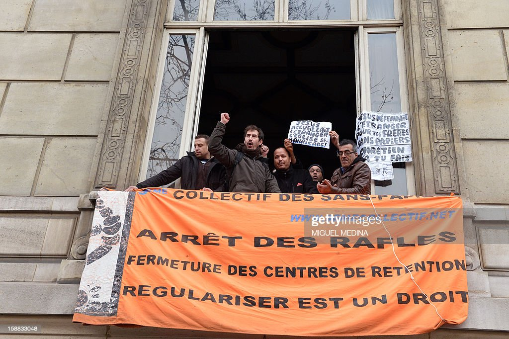 Members of organisations for the defense of illegal immigrants demonstrate with a banner reading 'Stop rafles. Close the retention centers' as they occupy the Vatican embassy (nonciature apostolique) in Paris, on December 31, 2012.