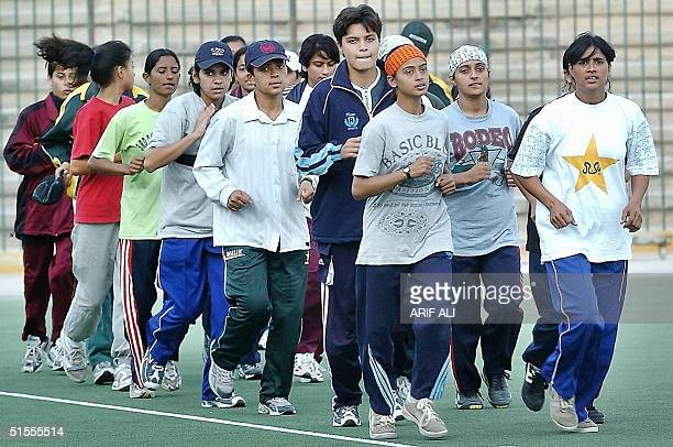 Members of Pakistan's women field hockey team run during a practice session at the National Hockey Stadium in Lahore 24 October 2004 The team is...