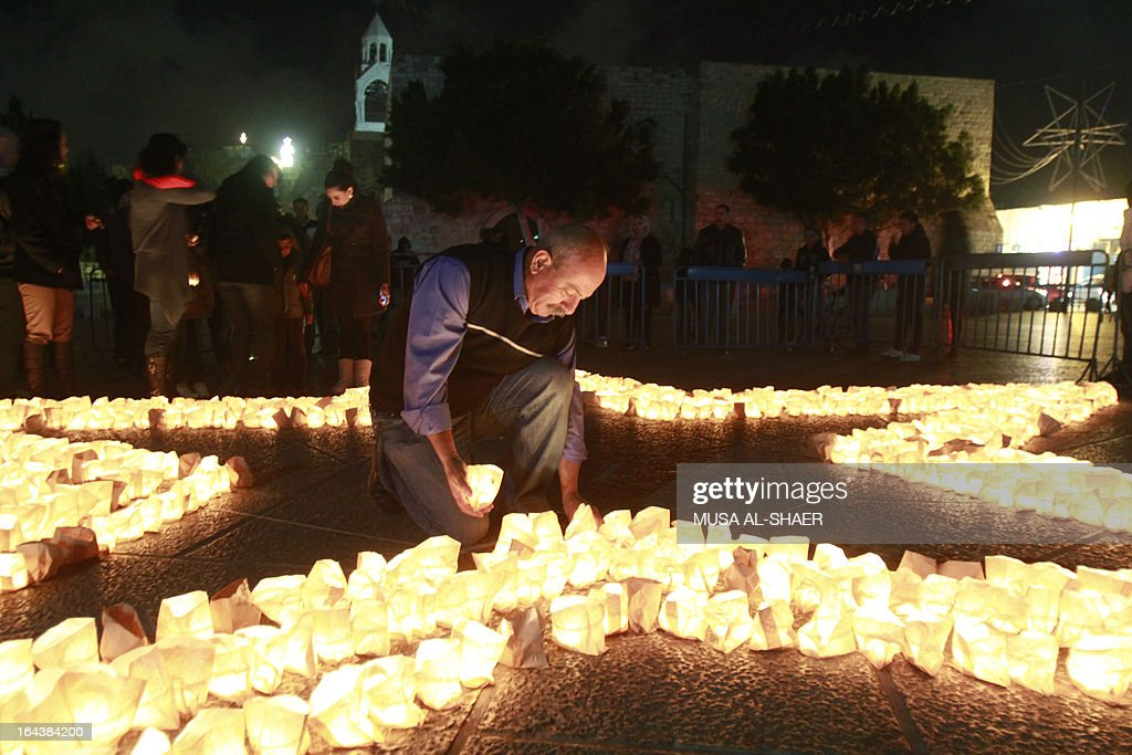 A members of Palestine Wildlife Society places a candle as he outlines the star of Bethlehem with candles at the Manager Square in front of the Church of the Nativity in the West Bank town of Bethlehem on March 23, 2013, to mark the Earth Hour for the first time in Palestine. Iconic landmarks and skylines were plunged into darkness as the 'Earth Hour' switch-off of lights around the world got under way to raise awareness of climate change.