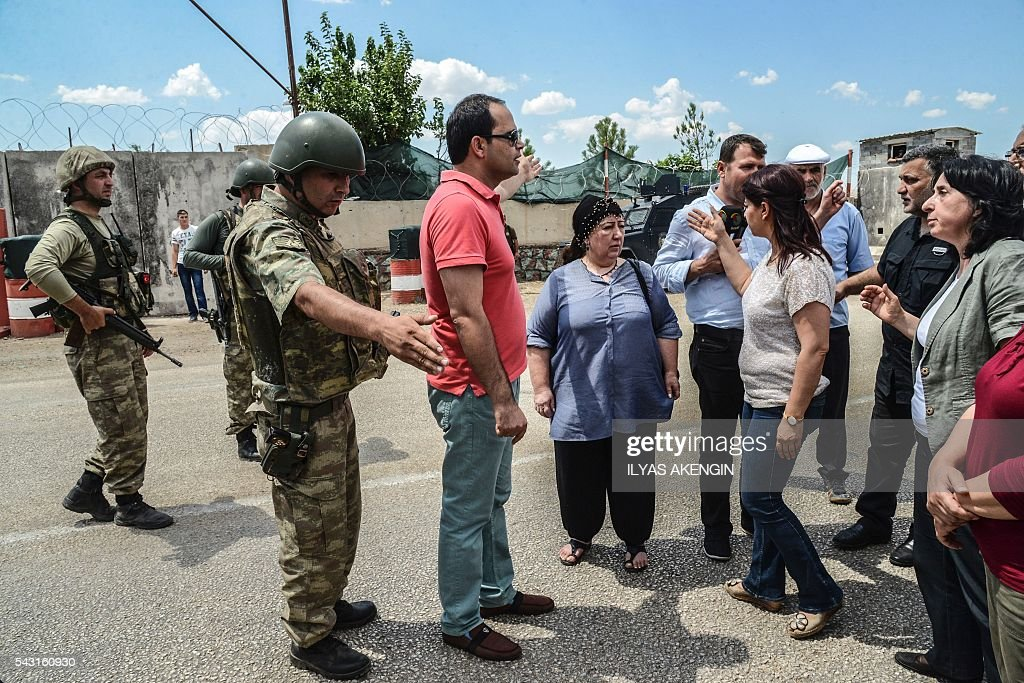 Members of Parliament of the pro-Kurdish Peoples' Democratic Party (HDP) and kurdish activists wait in a military check point as they want to enter Lice district in Diyarbakir on June 26, 2016. Militants from the outlawed Kurdistan Workers Party (PKK) on June 24, 2016 killed six Turkish soldiers in two separate attacks in the troubled southeast of the country, the army said. / AFP / ILYAS