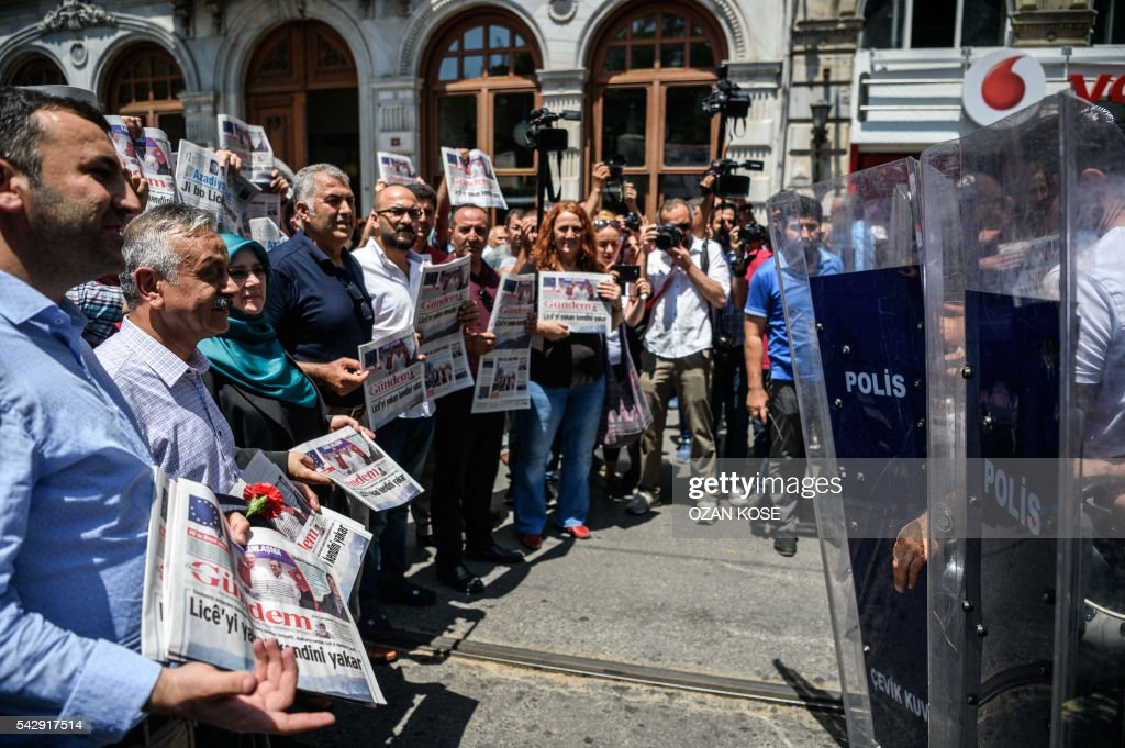 Members of Parliament of the pro-Kurdish Peoples' Democratic Party (HDP) hold copies of pro-Kurdish newspaper 'Ozgur Gundem' as they stand in front of a police barricade on June 25, 2016 in Istanbul during a protest against the arrest of three prominent activists for press freedom. Pro-Kurdish Turkish daily Ozgur Gundem has for weeks invited guest editors to take control of the newspaper, in a show of solidarity at a time when the government of President Recep Tayyip Erdogan is under fire for eroding press freedoms. The head of media rights watchdog Reporters Without Borders (RSF) on June 24 called for the release of the group's Turkey representative and two other activists held on 'terror propaganda' charges as he led a protest outside their prison in Istanbul. / AFP / OZAN