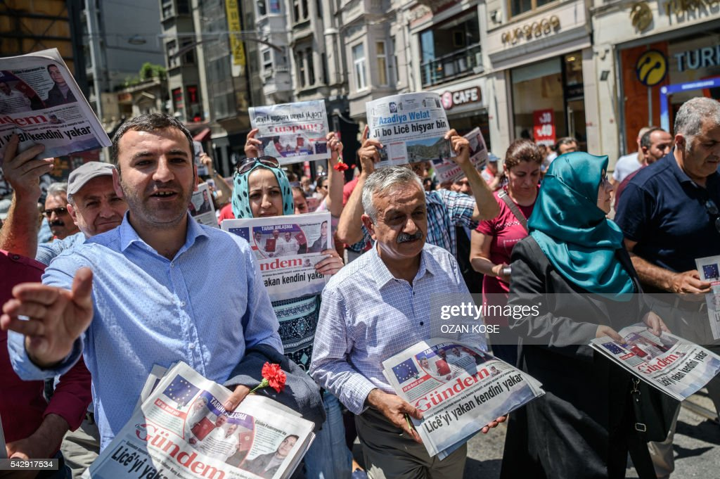 Members of Parliament of the pro-Kurdish Peoples' Democratic Party (HDP) hold copies of pro-Kurdish newspaper 'Ozgur Gundem' as they a protest against the arrest of three prominent activists for press freedom on June 25, 2016 in Istanbul. Pro-Kurdish Turkish daily Ozgur Gundem has for weeks invited guest editors to take control of the newspaper, in a show of solidarity at a time when the government of President Recep Tayyip Erdogan is under fire for eroding press freedoms. The head of media rights watchdog Reporters Without Borders (RSF) on June 24 called for the release of the group's Turkey representative and two other activists held on 'terror propaganda' charges as he led a protest outside their prison in Istanbul. / AFP / OZAN