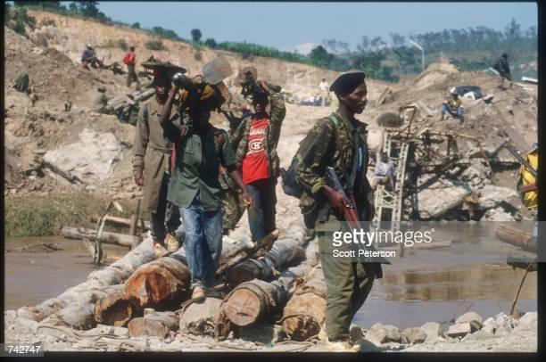 Members of Patriotic Front of Rwanda walk across a bridge over the Akanyaru river June 3 1994 in Rwanda They are preparing for the final offensive...