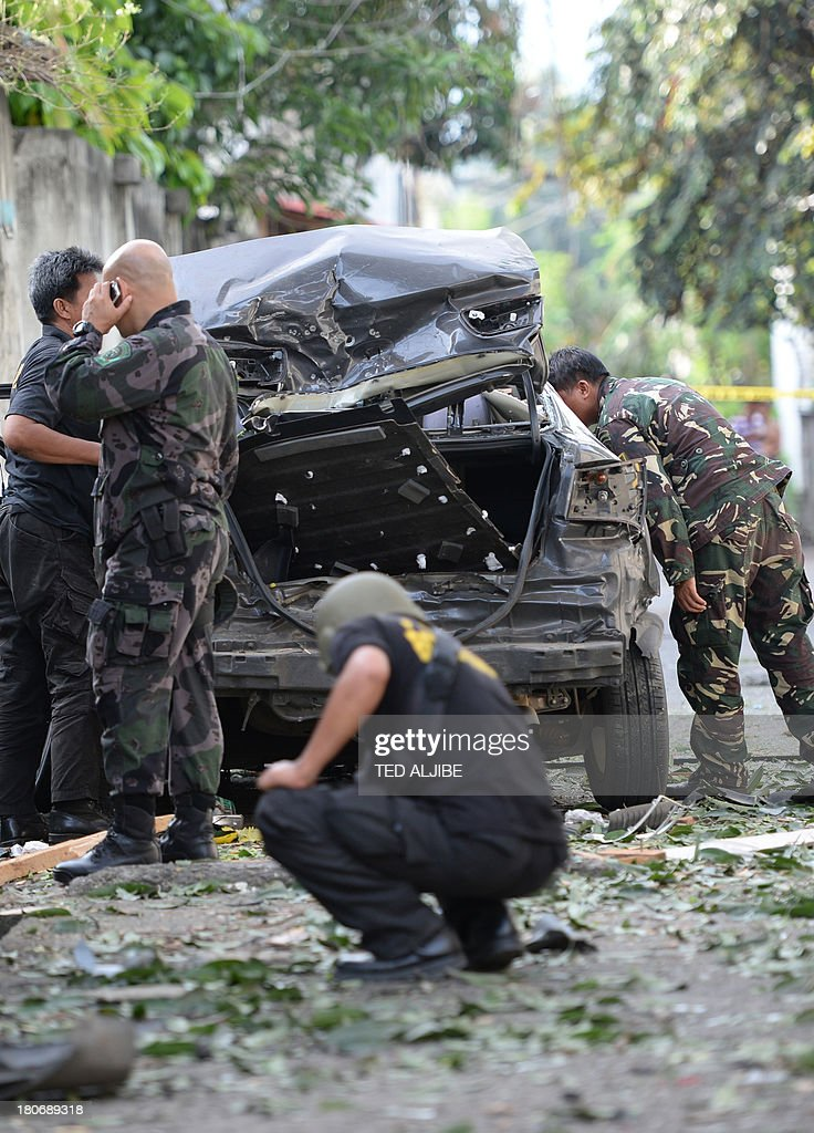 Members of Philippine police and military bomb squads look for evidence next to a destroyed car after a suspected car bomb explosion amidst heavy...
