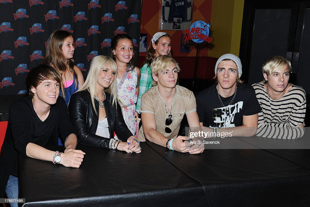 Members of R5 pose with fans during a visit to Planet Hollywood Times Square on September 2, 2013 in New York City.
