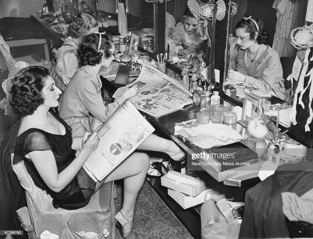 Members of Radio City Music Hall ballet corps work on Daily News crossword puzzle contest in their dressing room.