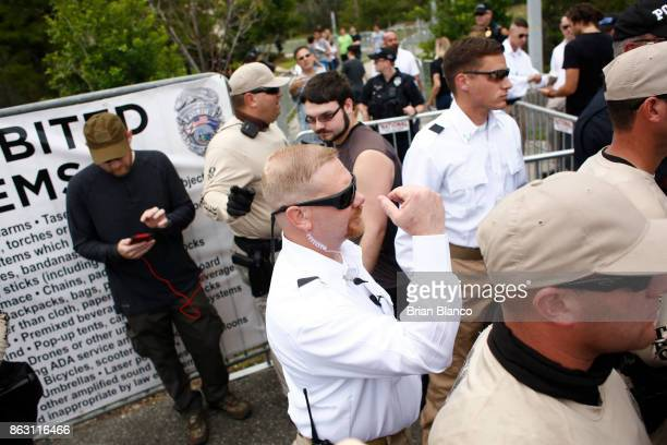 Members of Richard Spencer's security team in white stand behind police and decide who gets tickets to a speech by Spencer a white nationalist who...