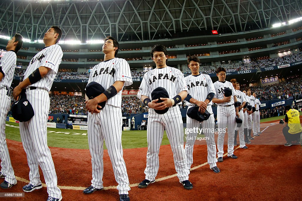 Members of Samurai Japan are seen on the base path during the playing of the Japanese National Anthem before the game against the MLB AllStars at the...