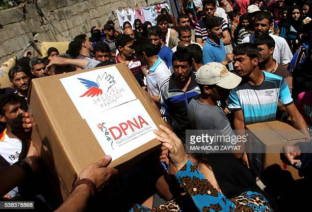 Members of Secours populaire a French nonprofit association deliver food aid to Syrian refugees in the village of AlAqibiya near Sidon in Southern...