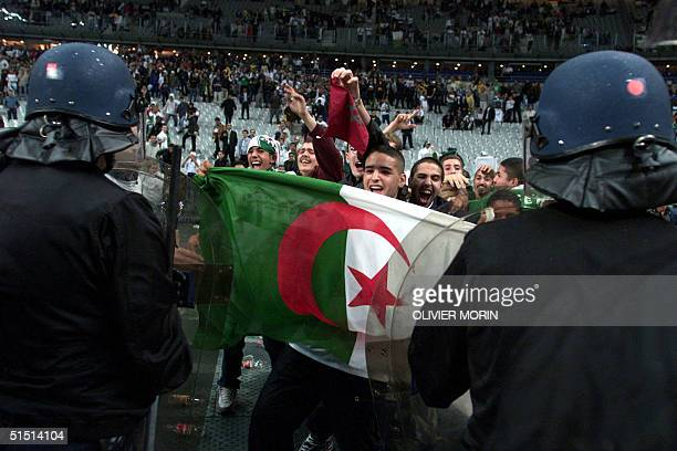 members of security forces try to contain supporters on the field during the friendly soccer match France vs Algeria at the Stade de France in...