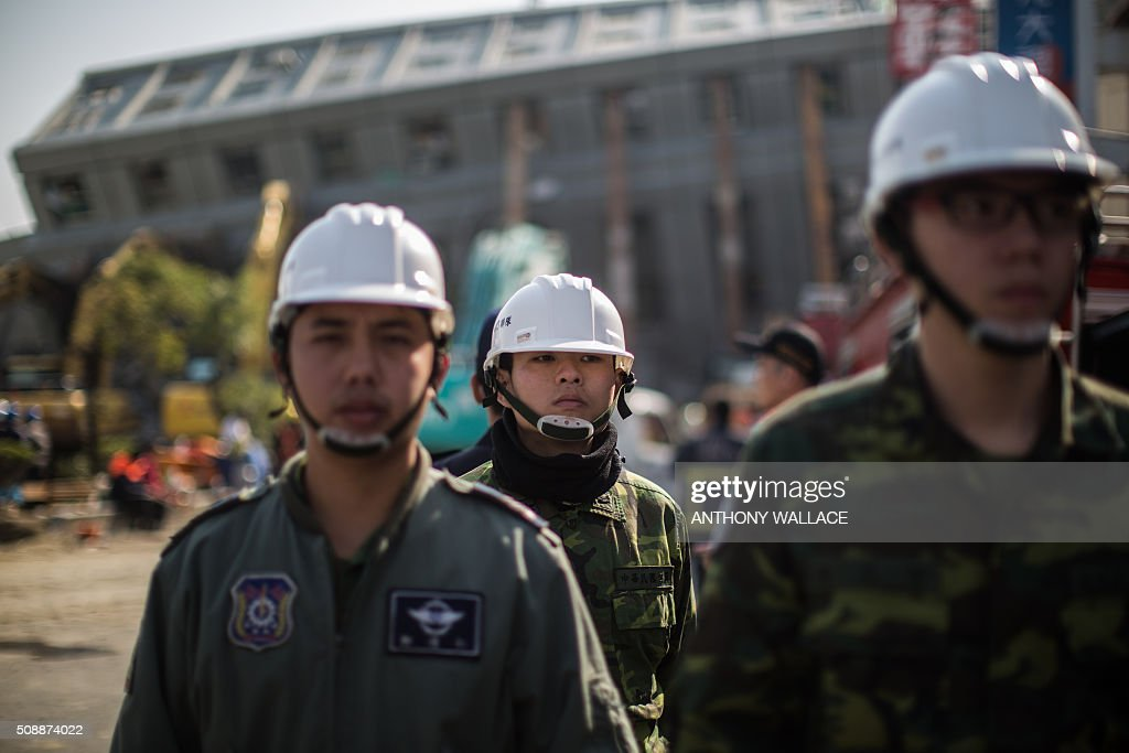 Members of security stand guard at a cordon set up around a collapsed building in the southern Taiwanese city of Tainan on February 7, 2016, following a strong 6.4-magnitude earthquake that struck early on February 6. Rescuers raced on February 7 to free more than 120 people buried under the rubble of an apartment complex felled by an earthquake in southern Taiwan that left 24 confirmed dead, as an investigation began into the collapse. AFP PHOTO / ANTHONY WALLACE / AFP / ANTHONY WALLACE