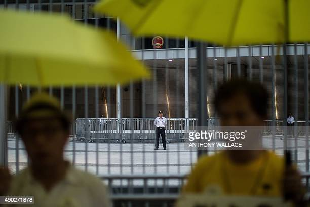 Members of security stand guard within the grounds of the government offices as activists hold yellow umbrellas a symbol of the prodemocracy movement...
