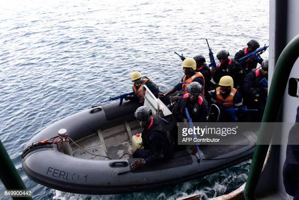 Members of Senegal's marines special forces come alongside the 'Casimir' a trawler suspected of illegal fishing during a mock exercise on September...