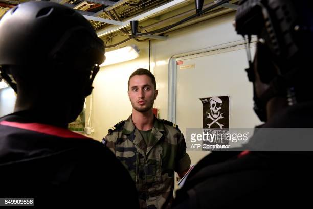 Members of Senegal's marines special forces listen to a French officer aboard the French Landing Helicopter Dock 'Dixmude' prior to take part in a...
