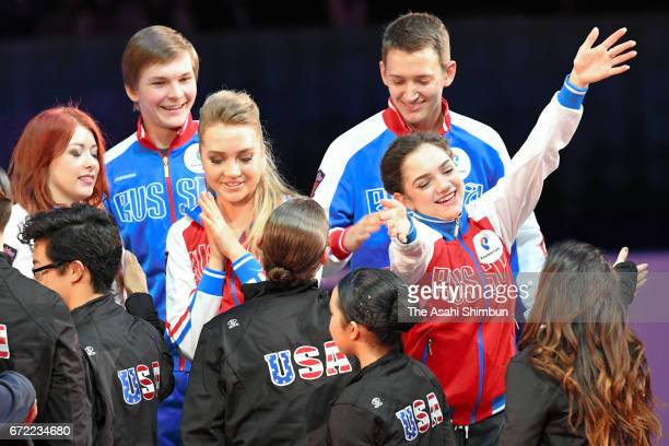 Members of silver medalists Russia and bronze medalists United States embrace at the medal ceremony during day three of the ISU World Team Trophy at...