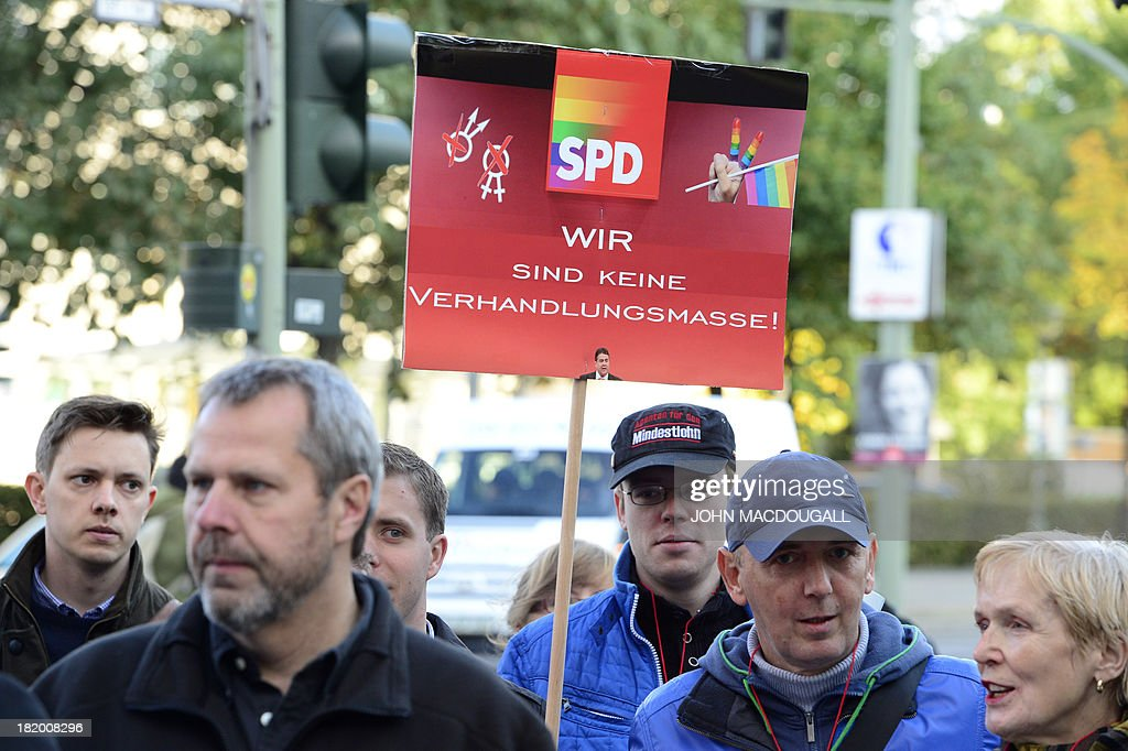 Members of Social Democratic Party (SPD) hold a poster reading 'We are no negociation's object' while demonstrating in front of the SPD's headquarters on September 27, 2013 where a meeting on a 'grand coalition' takes place. Germany's opposition Social Democrats hold a mini-party conference to discuss behind closed doors overtures by Chancellor Angela Merkel for a left-right 'grand coalition' after her conservatives won weekend elections but fell short of an outright majority MACDOUGALL