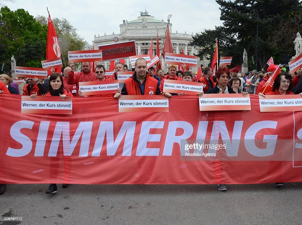 Members of Social Democratic Party holding banners saying 'Werner, you are in right way' attend a rally to mark May Day, International Workers' Day, in front of municipal building in Vienna, capital city of Austria on May 1, 2016.