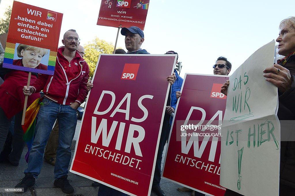 Members of Social Democratic Party (SPD) holding electoral campaign posters and poster displaying the rainbow colours while demonstrating in front of the SPD's headquarters on September 27, 2013 where a meeting on a 'grand coalition' takes place. Germany's opposition Social Democrats hold a mini-party conference to discuss behind closed doors overtures by Chancellor Angela Merkel for a left-right 'grand coalition' after her conservatives won weekend elections but fell short of an outright majority MACDOUGALL