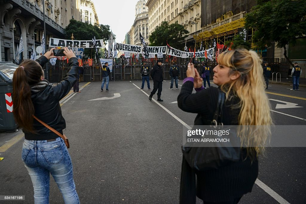 Members of social organizations demonstrate behind a security fence in the surroundings of the Metropolitan Cathedral as President Mauricio Macri attends the Te Deum to commemorate the 206th anniversary of the May Revolution, in Buenos Aires, on May 25, 2016. / AFP / EITAN